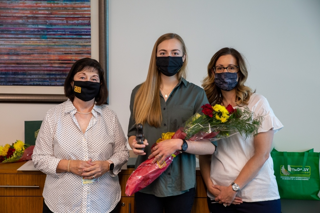 Three masked women pose for a photo, the middle one holding flowers