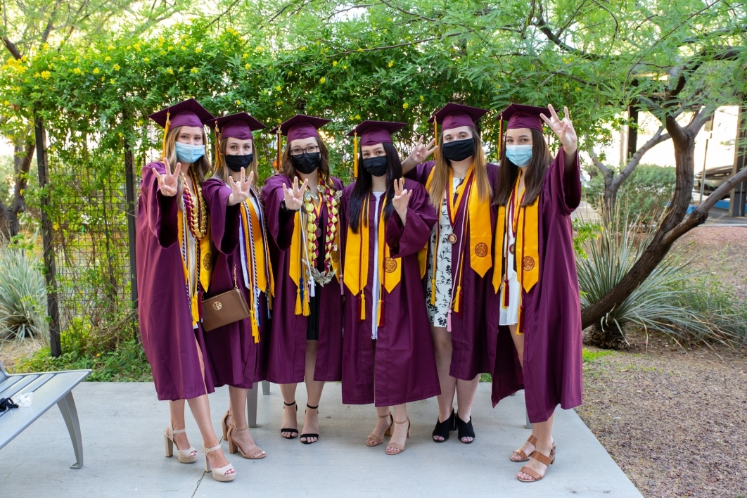 A group of women in graduation gowns pose with the pitchfork gesture