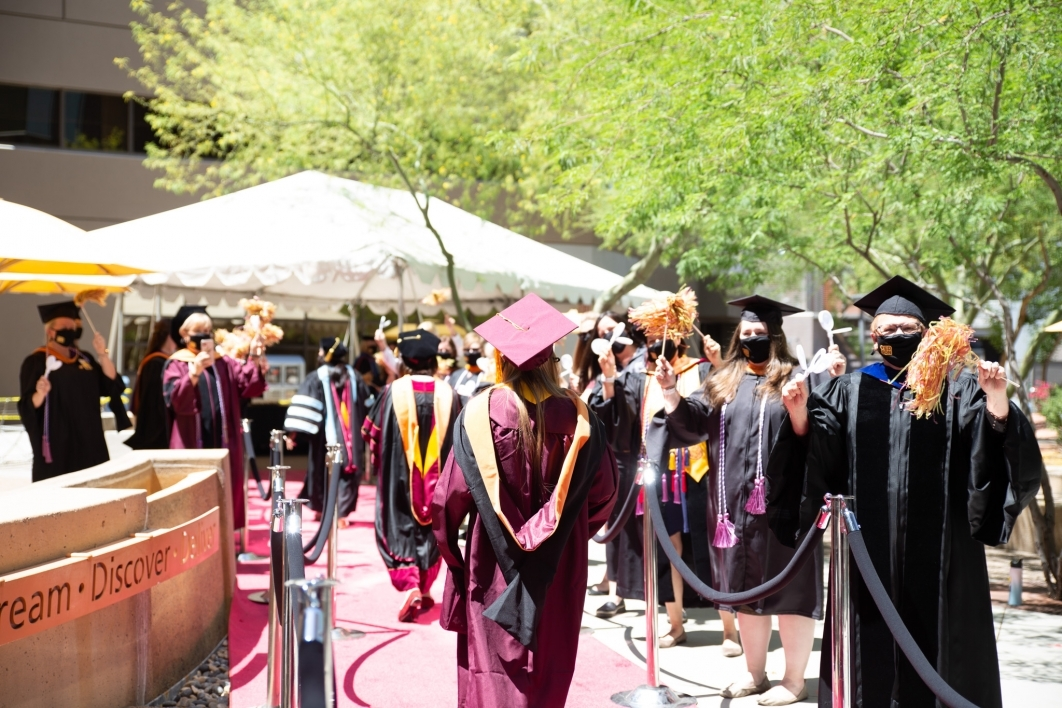 Graduating students walk through a roped off walkway while being cheered on by faculty in graduation regalia