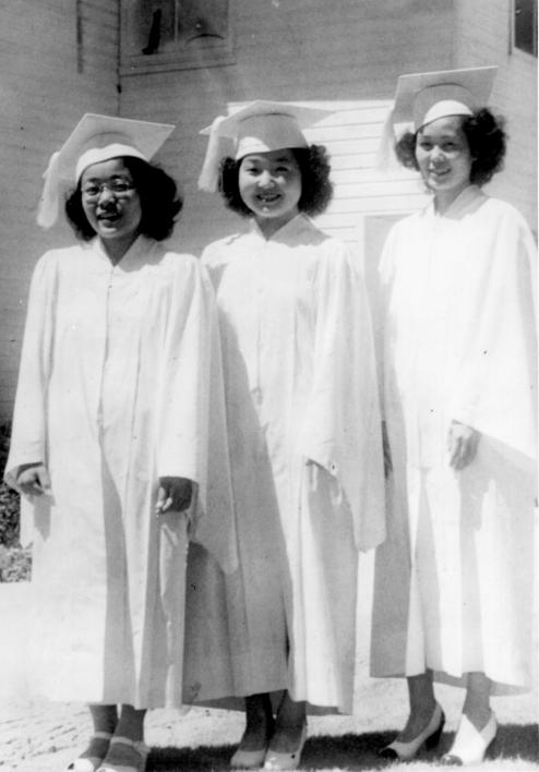 three girls in high school caps and gowns