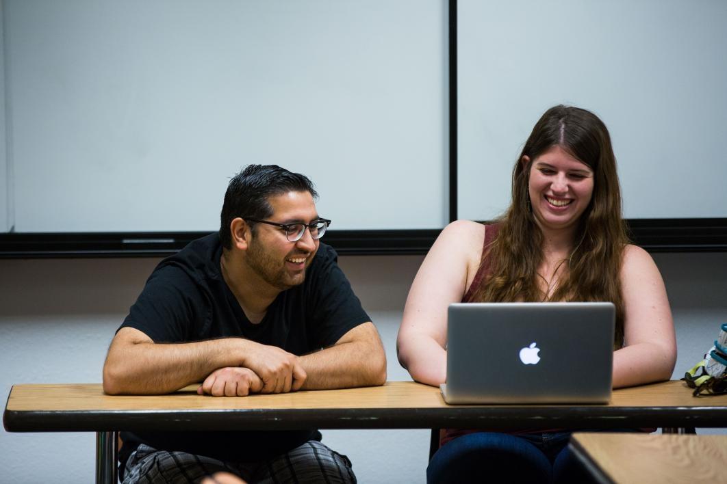 two student editors talking and looking at latptops