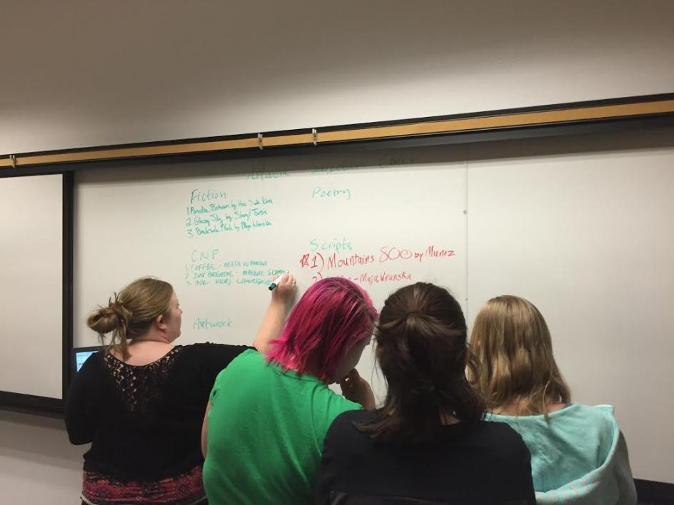 backs of heads of students grouped at whiteboard