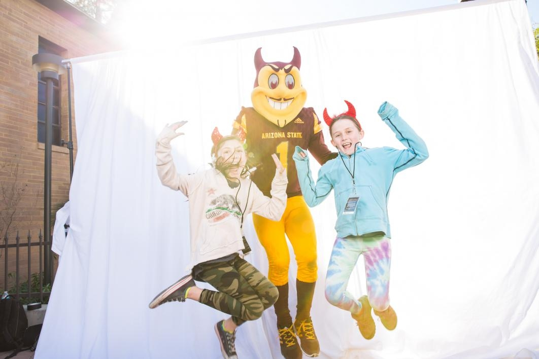 Two girls jump with Sparky in a photo-booth photo.
