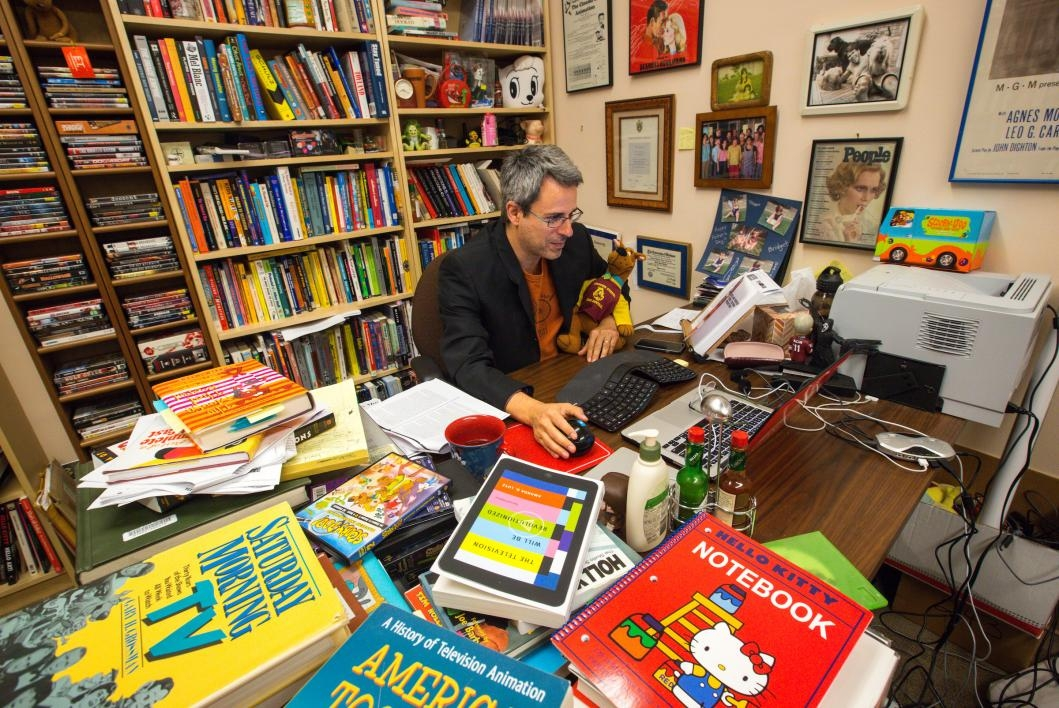 Kevin Sandler surrounded by books in his small office