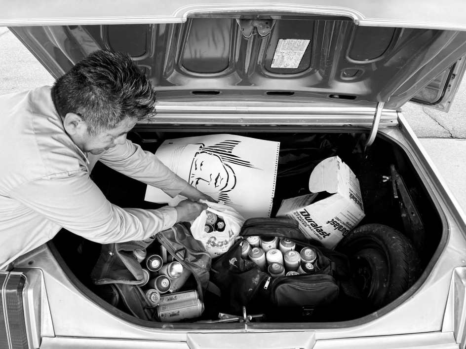 Douglas Miles pulling painting supplies from his trunk.