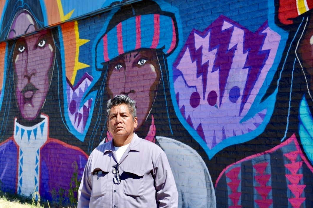 Douglas Miles standing in front of one of his murals that features three Apache figures