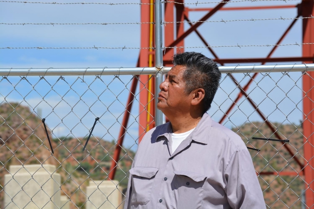 Douglas Miles photographed in front of a chain fence