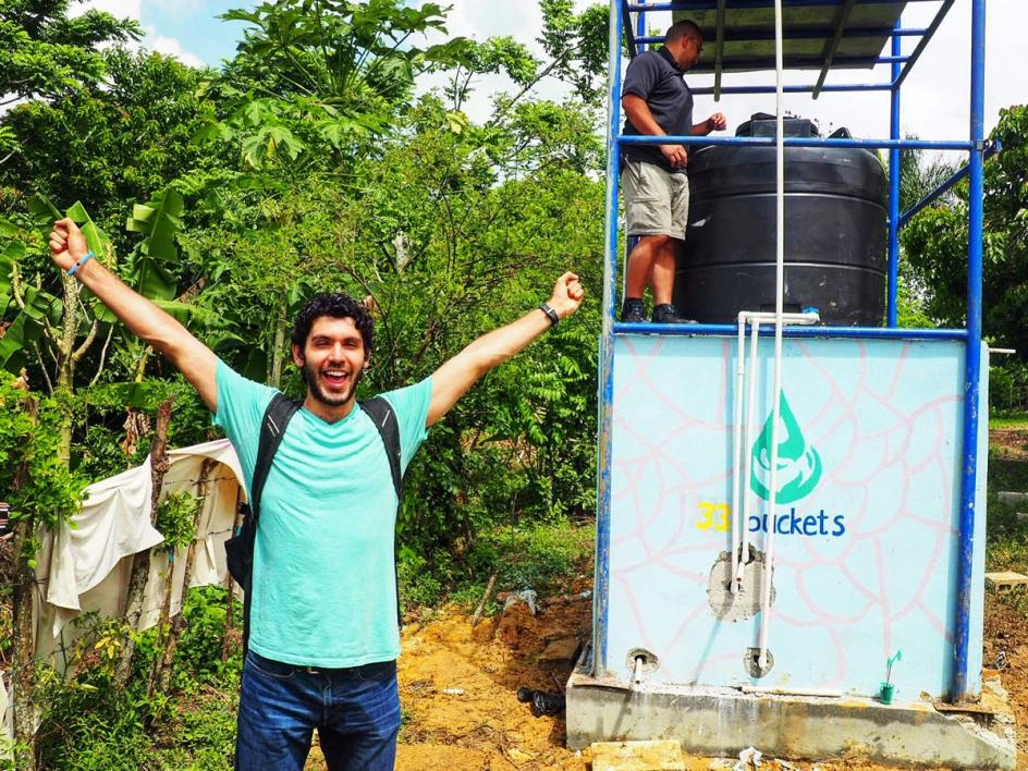 Mark Huerta celebrates in front of the finished water filtration system in the Dominican Republic.