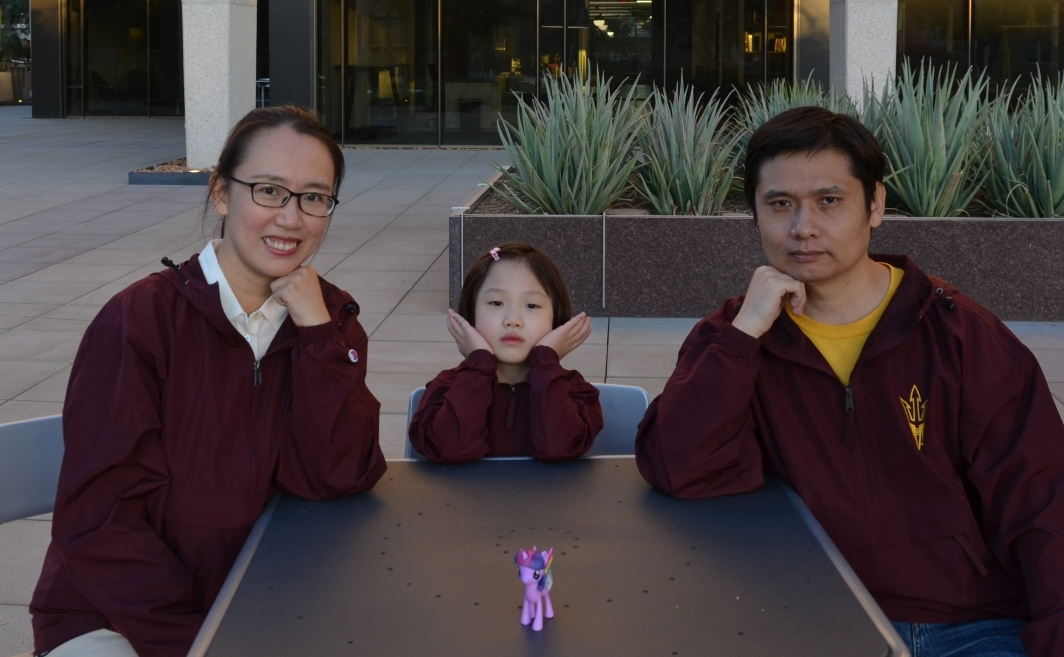 Two parents and a little girl sit at a table looking at the camera