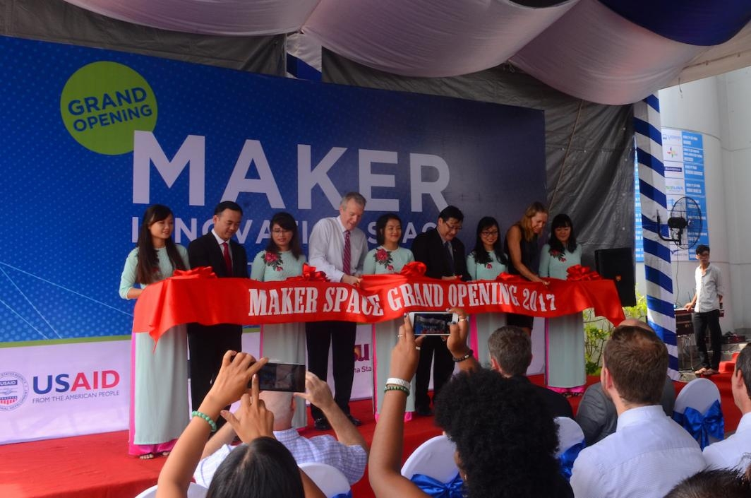 Photo of nine people behind a red ribbon that say Maker Space Grand Opening 2017.