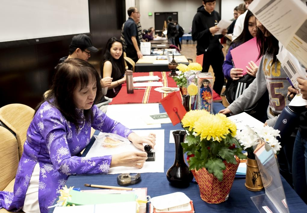 ASU Vietnamese language lecturer Thuy-Kim Le writes names in Vietnamese ink calligraphy for visiting students at the ASU Language Fair.