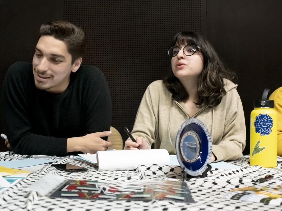 ASU students Lermon Montoya and Evanna Rouhani volunteer at the Arabic language table, writing in Arabic and answering program questions for visiting high school students.