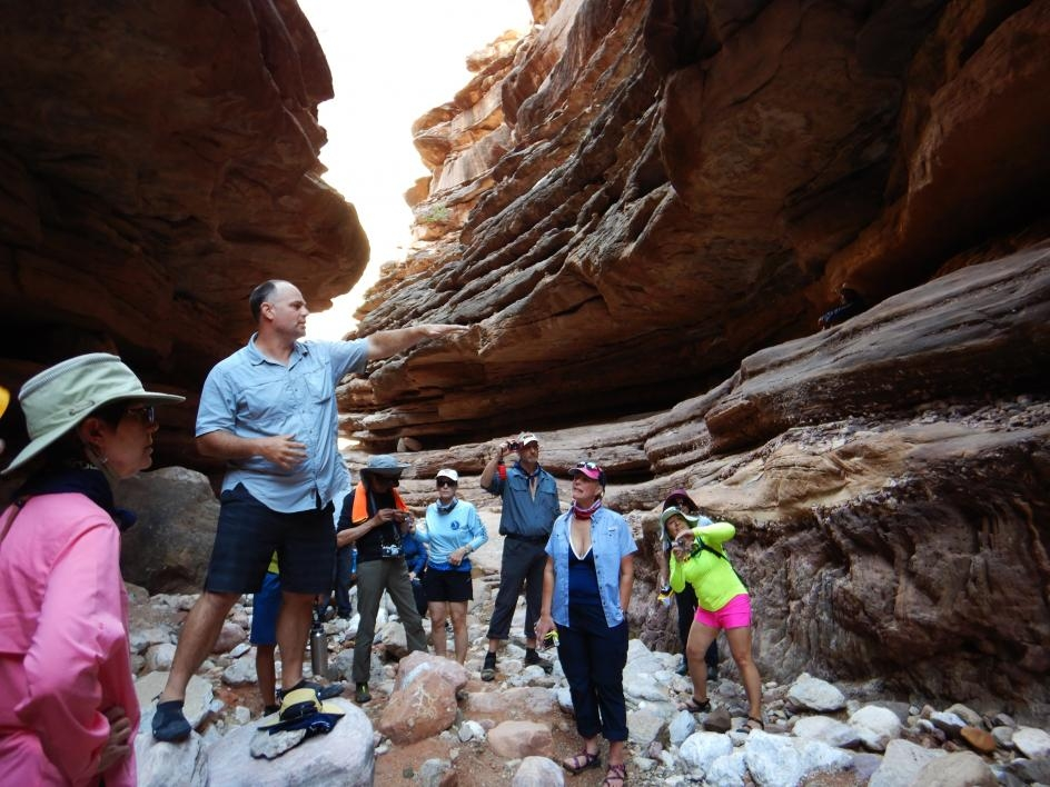 Chris Campisano, an associate professor in The College's School of Human Evolution and Social Change, points out a geological formation on the canyon wall called the Great Unconformity to passengers on the trip.