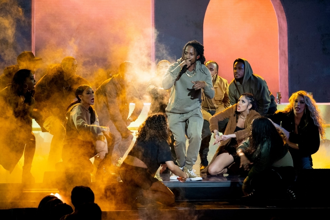D Smoke performs on stage surrounded by dancers in a cloud of smoke