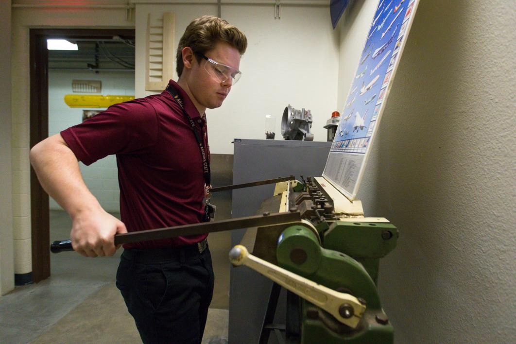 Aviation student Eamonn McIntyre bends a piece of metal in a machine.