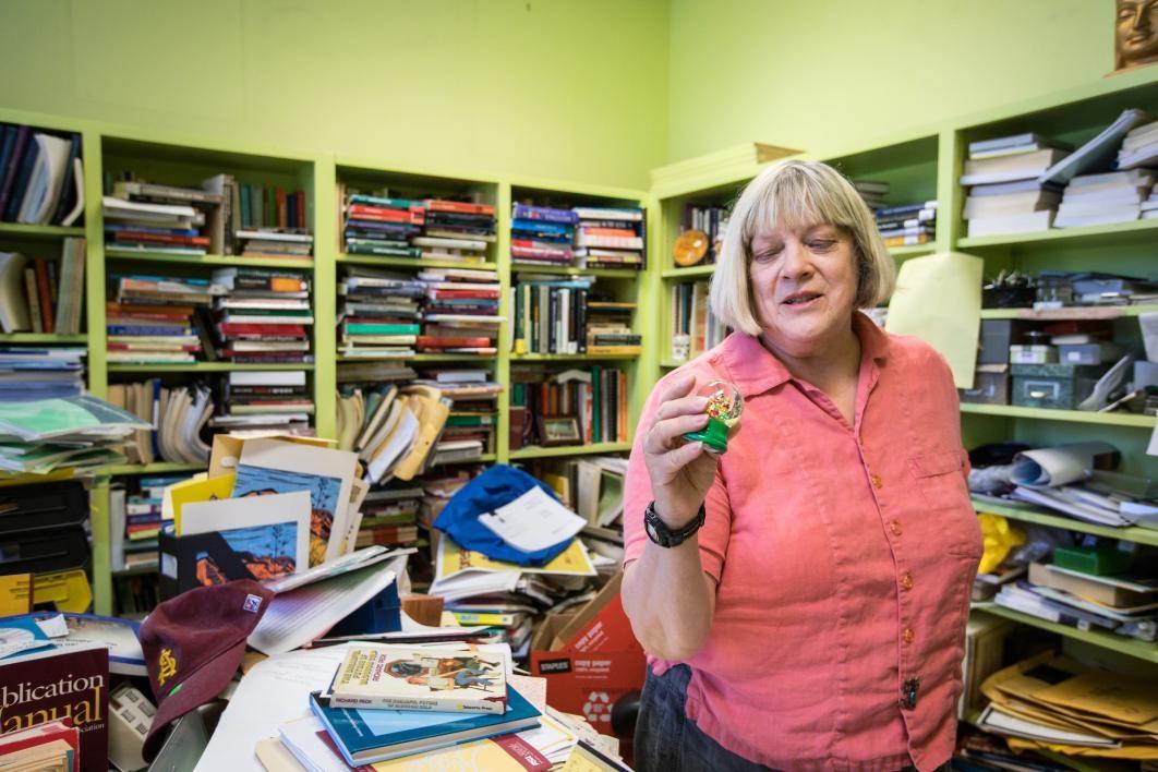 Professor Karen Adams looks at a snowglobe in her book-filled office