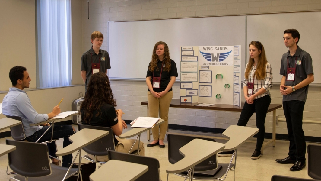 Seth Mazza (right) helps an EPICS High team he mentors present at an EPICS High showcase.