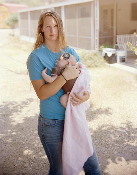 Photograph by Pam Golden shows a blonde woman holding a baby.