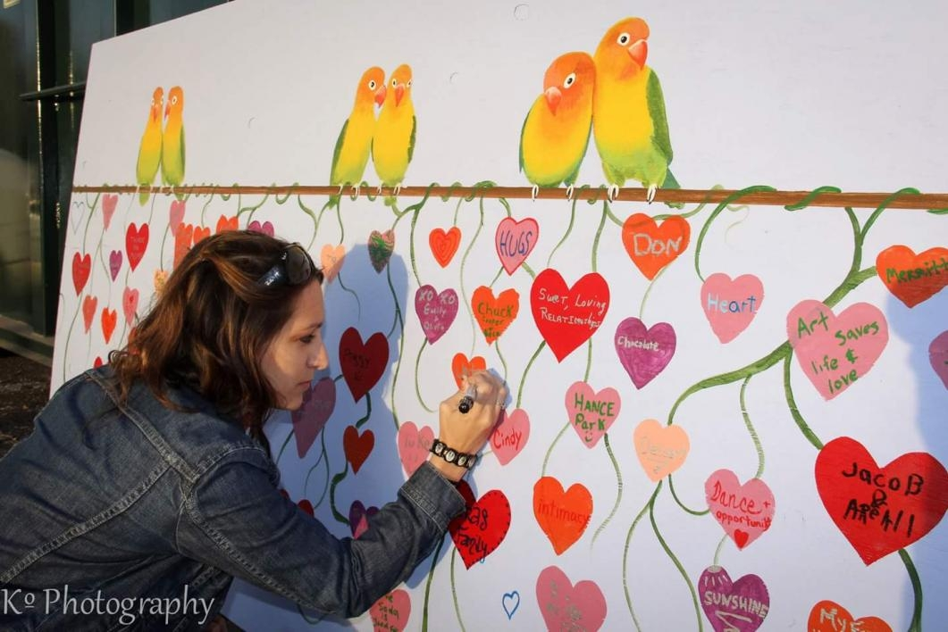 Kira signing a painted heart among others on a colorful mural