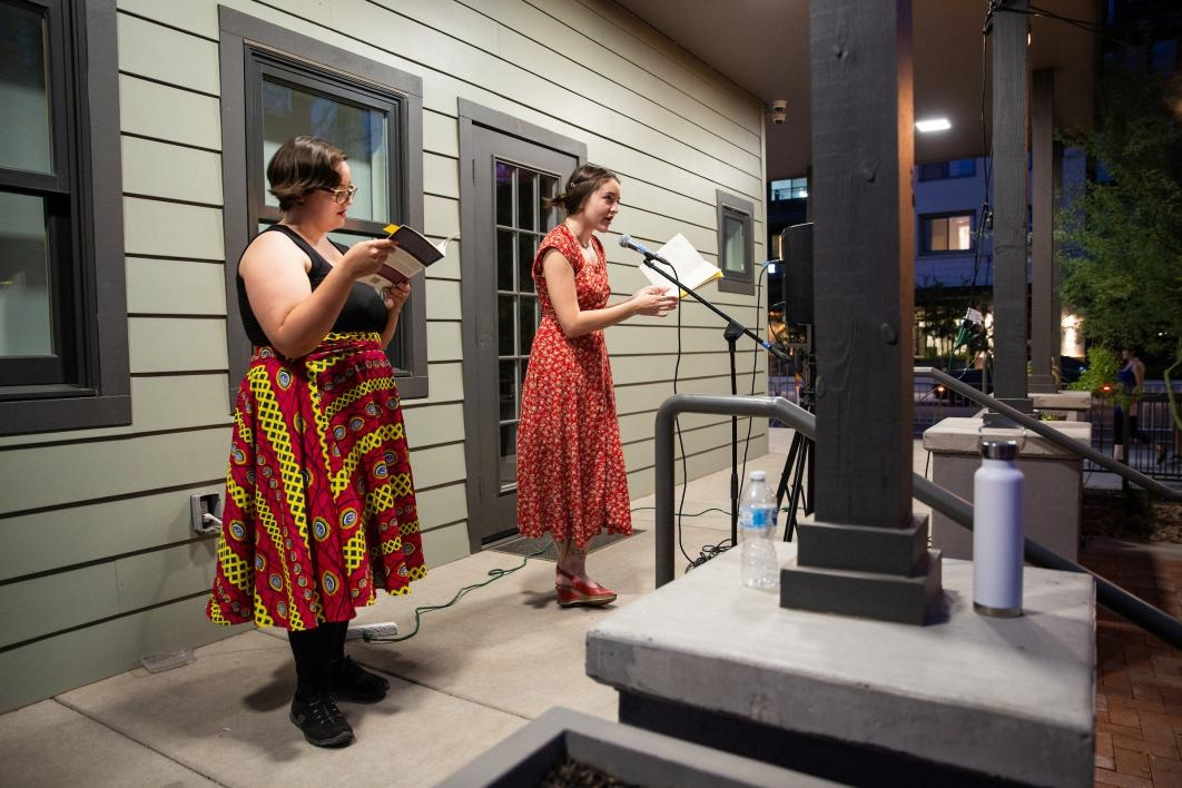 two women reading poetry into microphones on a porch
