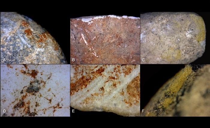 Magnified photo of red and yellow ochre traces on stones