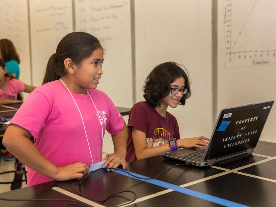 Two girls work at a laptop to program their robot.