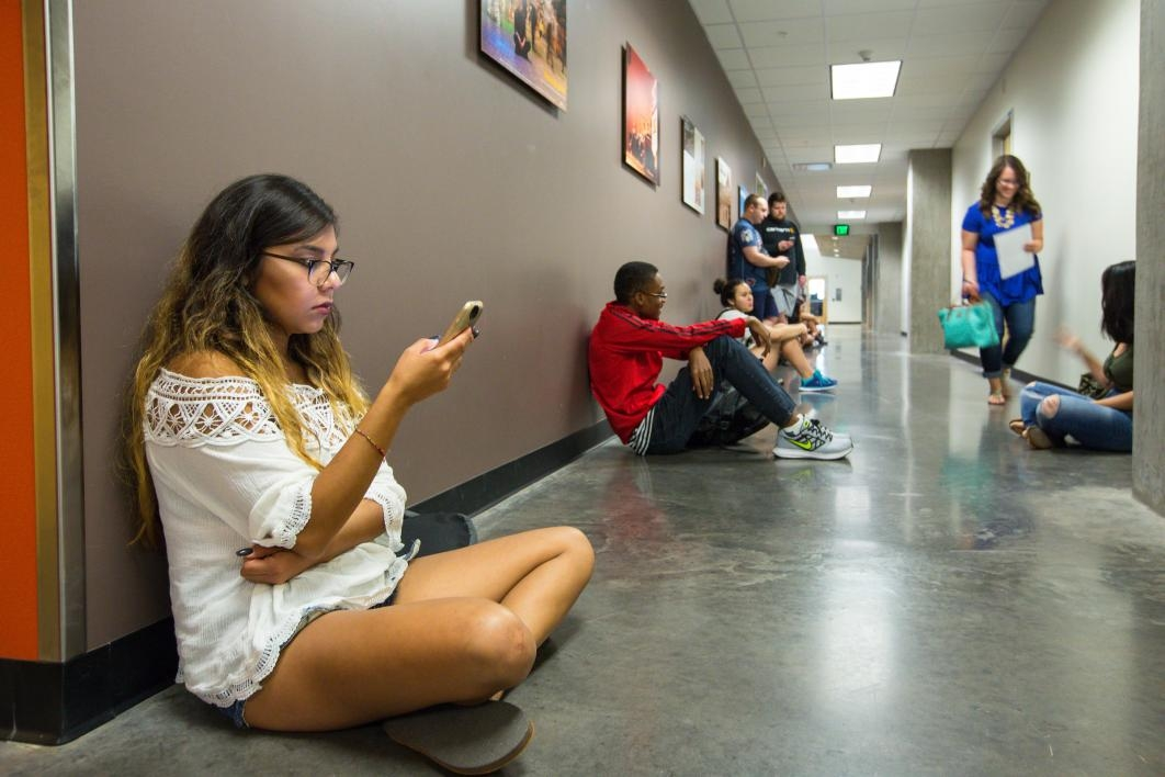 Student sitting in hallway looking at phone