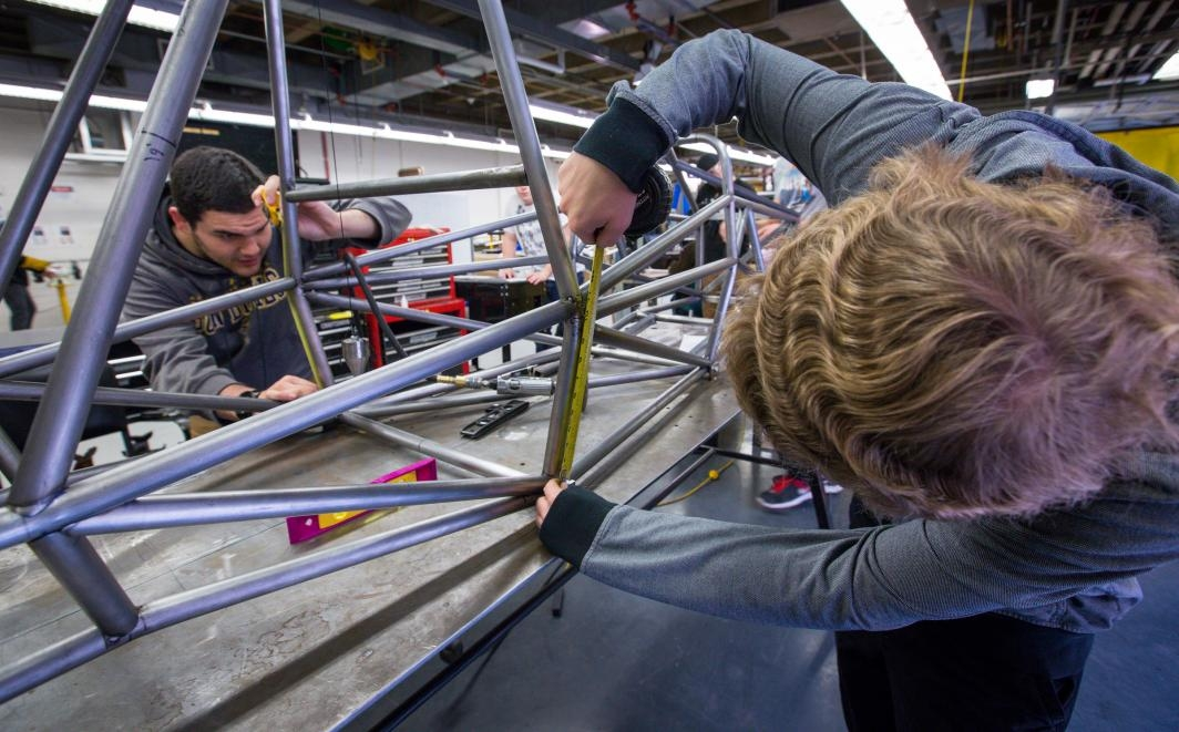 Students work on the chassis to a race car.