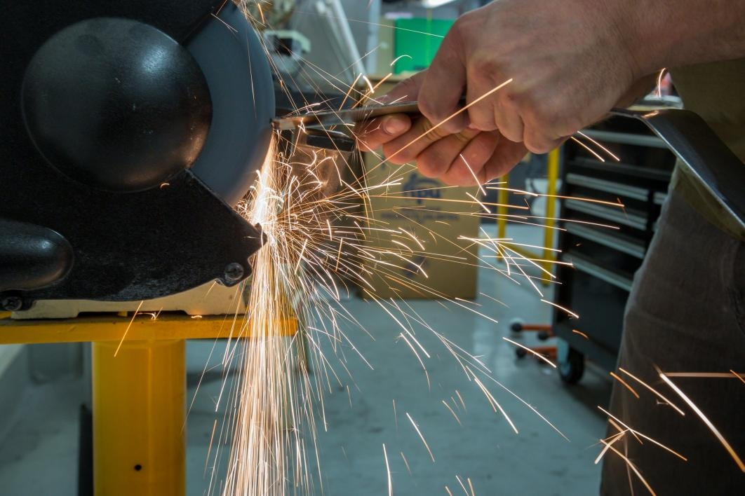 A student grinds down car parts amid a spray of sparks in the Formula SAE club's shop.