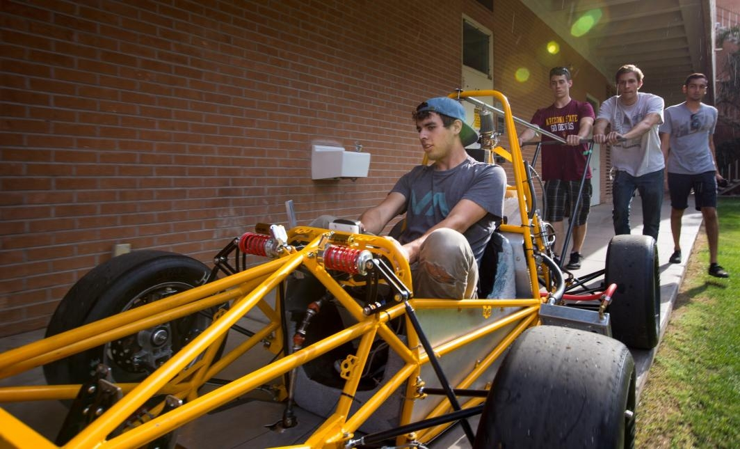 Students roll their race car through campus to load it onto a trailer.