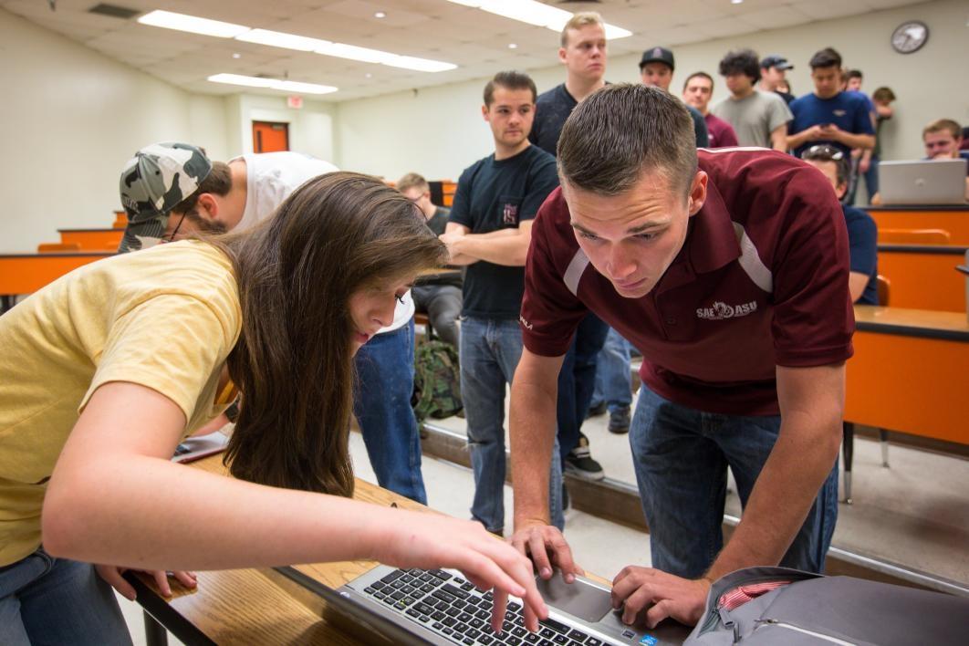 Students type on laptops.