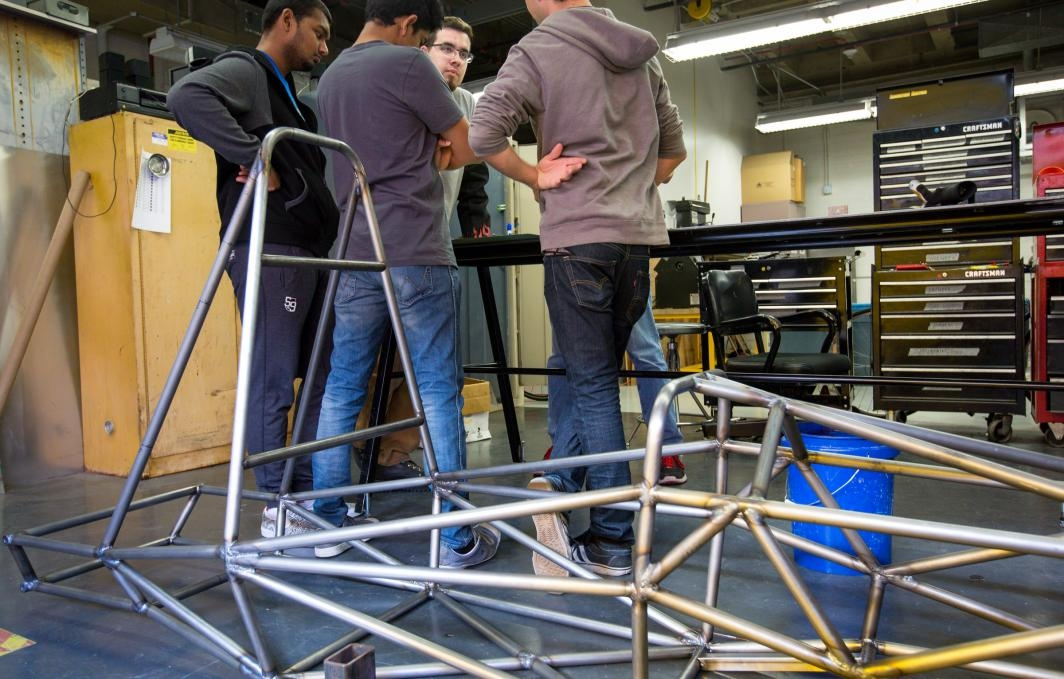Formula SAE students with the car's chassis.