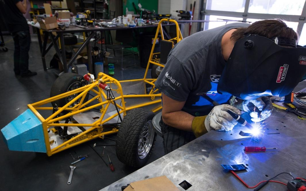 A student welds a car part in the Formula SAE team's shop.