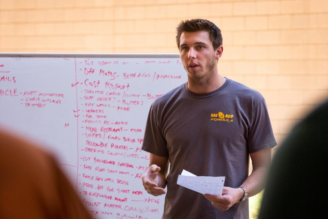The leader of the student race car team goes over the day's to-do list.