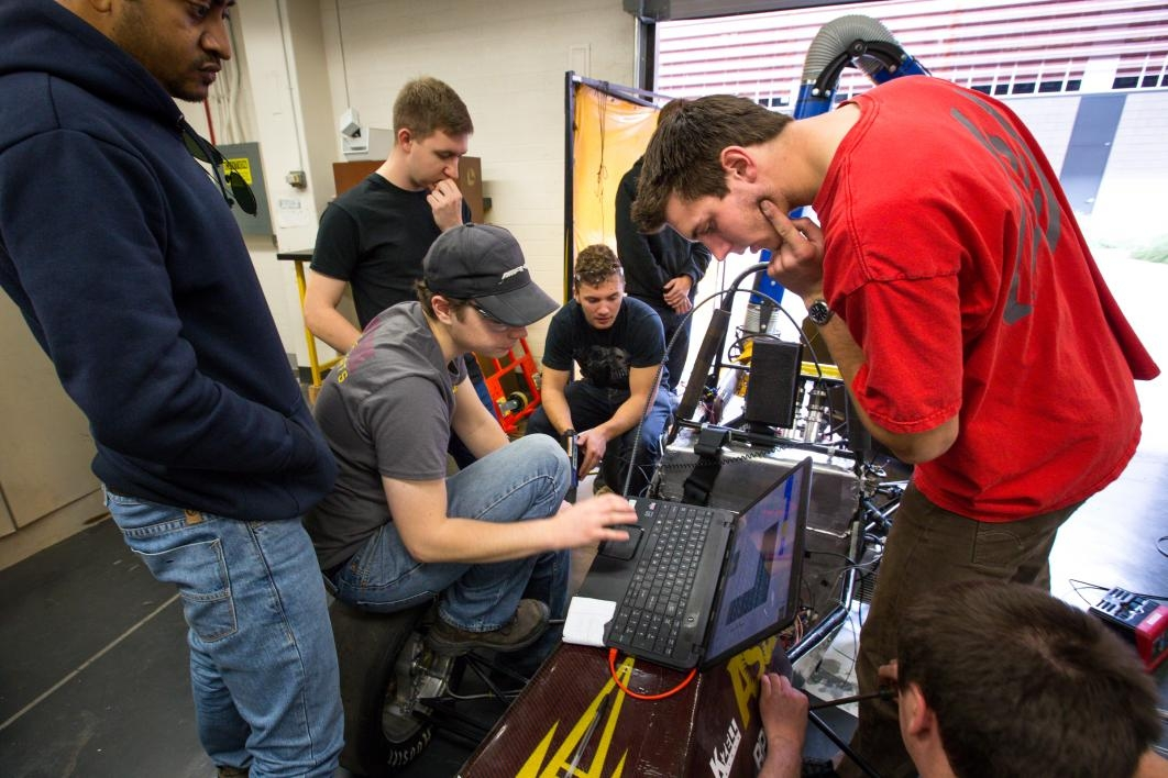 Formula SAE students gather around a computer.