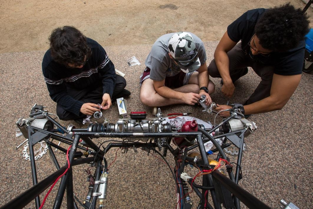 Formula SAE students work on the car's brakes.