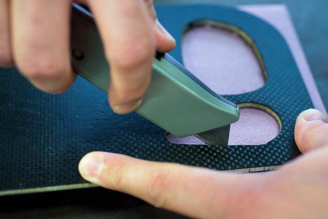 Hands use a sharp knife to cut out a steering wheel assembly.