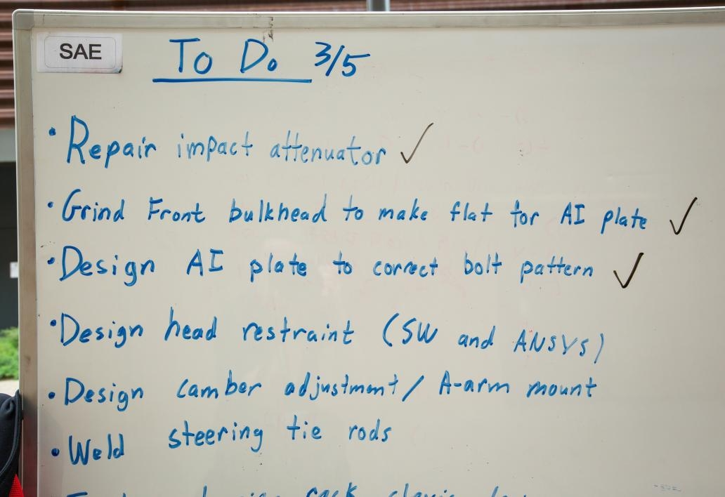 A to-do list on a whiteboard in the Formula SAE race car workshop.