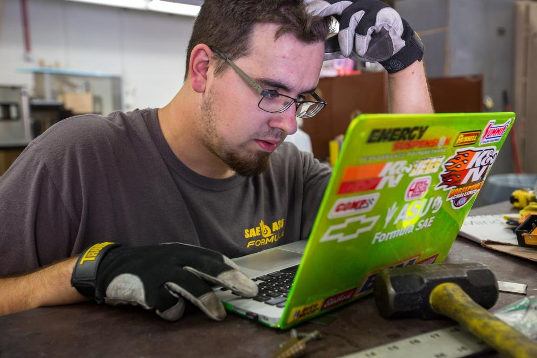 A student engineer works at a laptop in the Formula SAE club's shop.