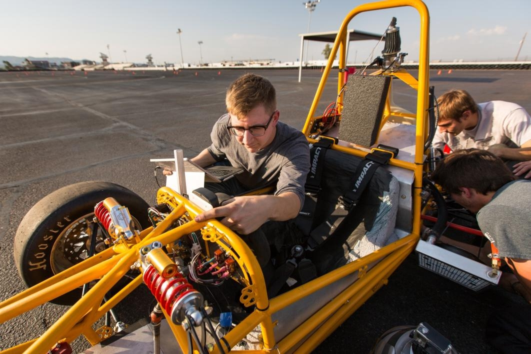 Students run diagnostics on the race car on the test track.