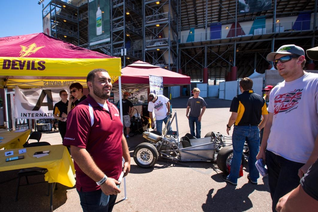 A crowd looks at the in-progress car being built by ASU students.