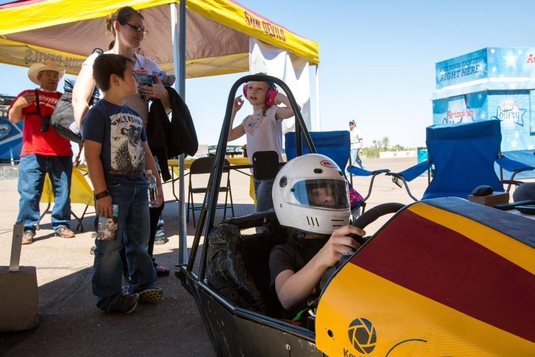 A young child plays in a race-car simulator.
