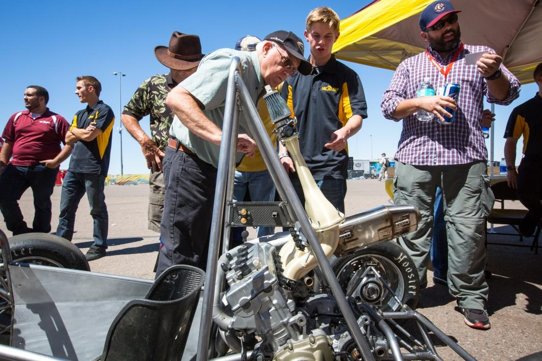 An older man checks out the in-progress race car built by ASU students.