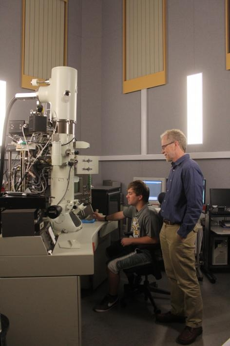 Two men stand next to a large microscope