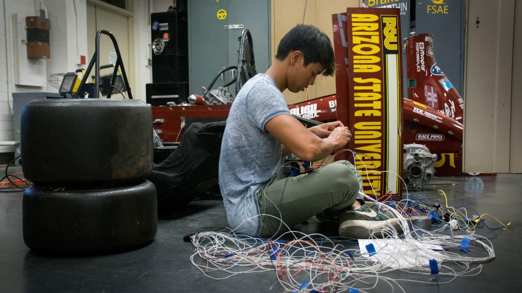 ASU student Gavin Charoenmin works on a wiring harness for the SAE race car
