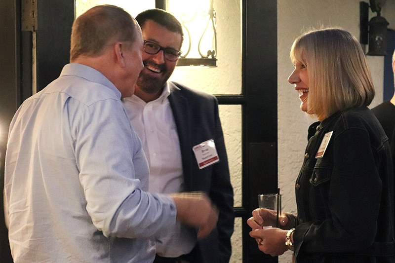 people wearing name tags, smiling and chatting at a networking event