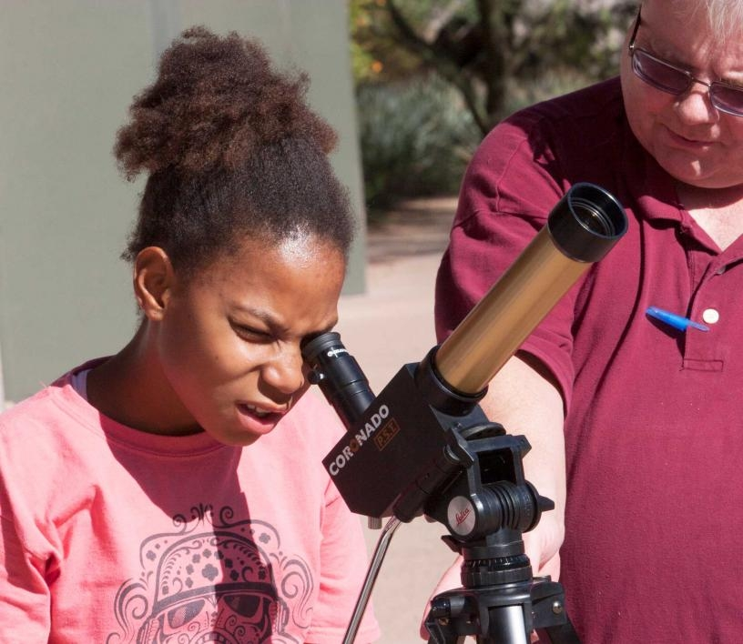 Scout looks at the sun through a telescope at ASU Polytechnic campus