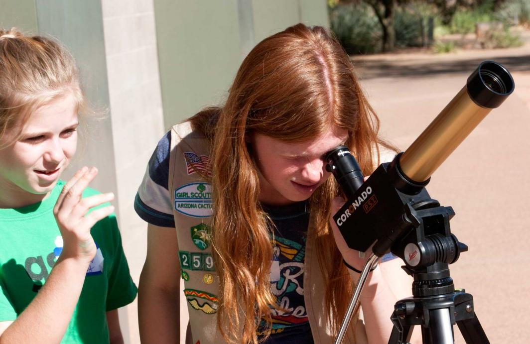 Scout gives pointers to friend as she looks at the sun through a telescope at ASU Polytechnic campus