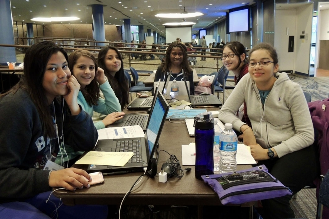 Group of girls gather around computers during a Hackathon in 2016