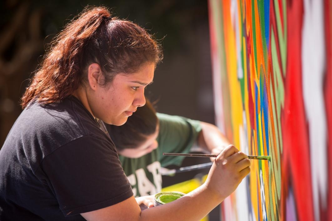 Erica Guerrero painting on mural